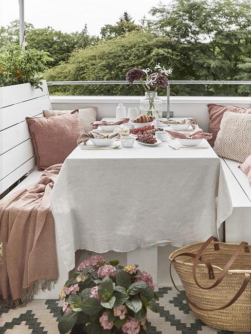 klein balkon inrichten met witte houten banken en tafel met natuurtinten accessoires