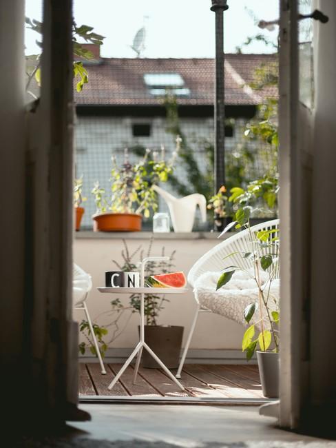 Openslaande deuren naar het balkon met wit gevlochten stoelen en klein rond tafeltje