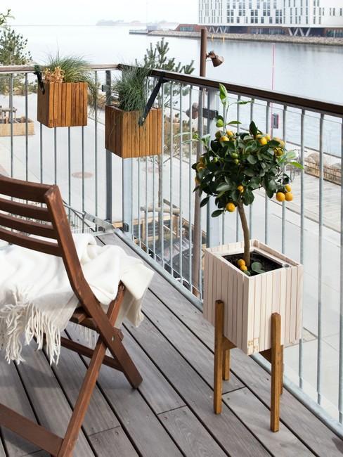 Balkon hangplanten aan balkonrailing met houten klapstoel en witte deken
