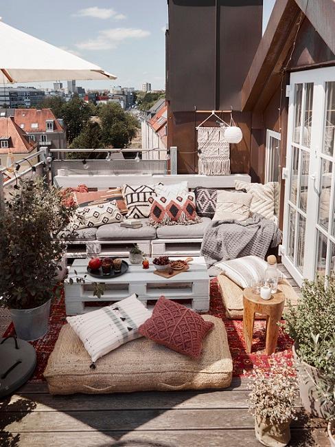Balkon met pallet loungebank en tafel met rotan poef en gekleurde kussens