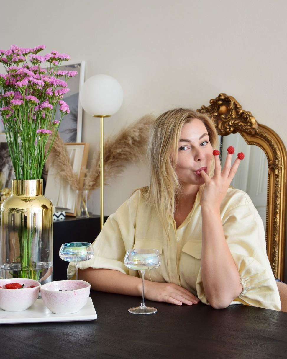 Vivian Hoorn aan donker houten keukentafel met rasberrys aan haar vingers