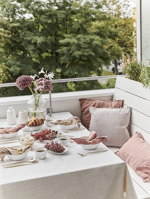 balkon decoreren met roze kussens op een witte buitenbank