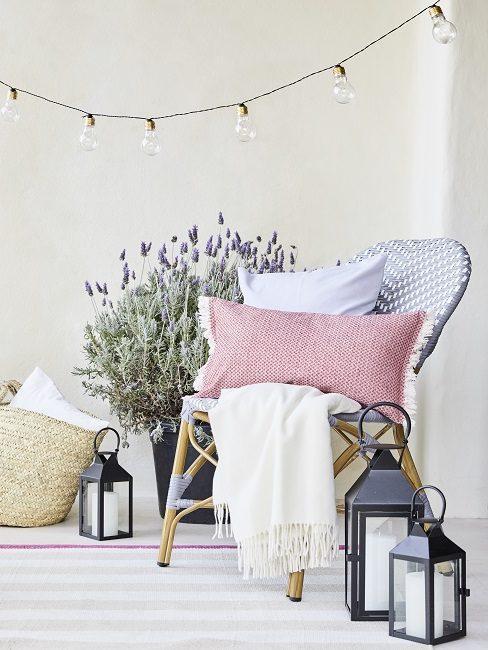 balkon decoratie met roze kussens en lampenslinger