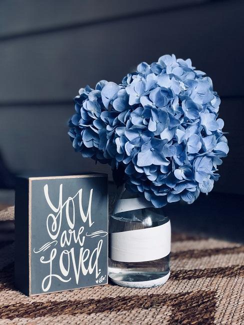 Blauwe hortensia in bloemenvaas voor zwarte houten muur met kaartje