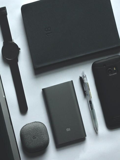 Witte tafel met zwarte accessoires en gadgets