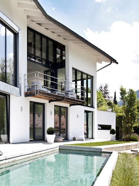 Moderne tuin met zwembad bij wit huis met donker houten kozijnen