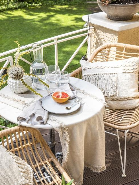 Balkon met rotan eetstoelen aan kleine ronde tafel