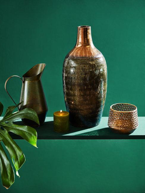 bronzen waterkan, vaas en windlichten op groene achtergrond