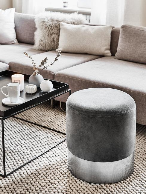 Zilveren velvet poef met grijze bank en zwarte salontafel