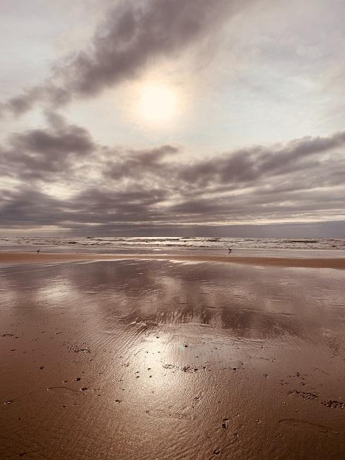 Nat strand met wolken