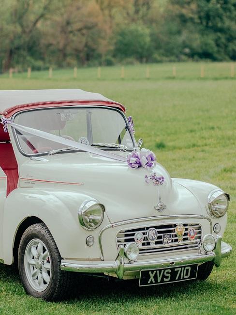 Huwelijksdecoratie met bloemen op een witte auto