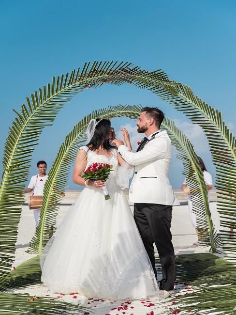 Bruidspaar naast de groene huwelijksdecoratie