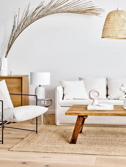 witte bank met een houten tafel en beige stoel met zwarte poten