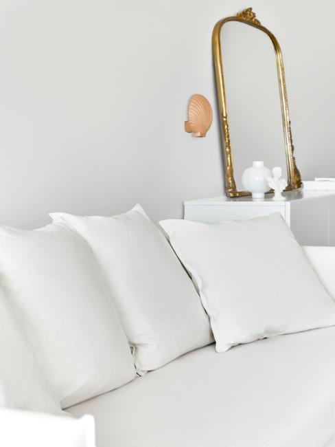 witte bank met witte kussens en gouden spiegel
