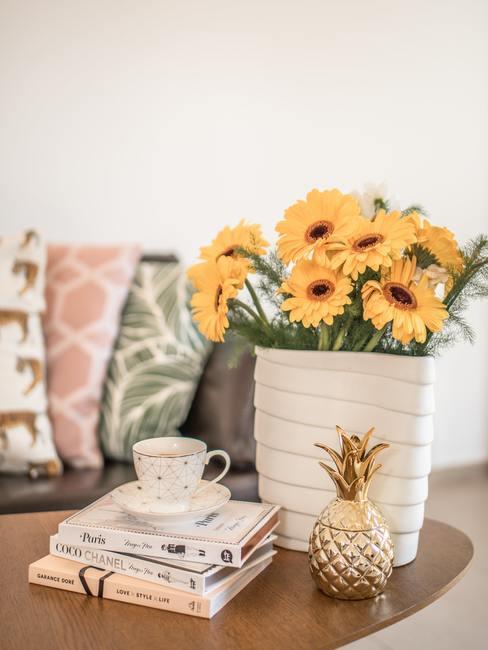 Zonnebloemen in een witte vaas naast boeken, koffiekopje en decoratieve ananas op de achtergrond van kleurrijke kussens