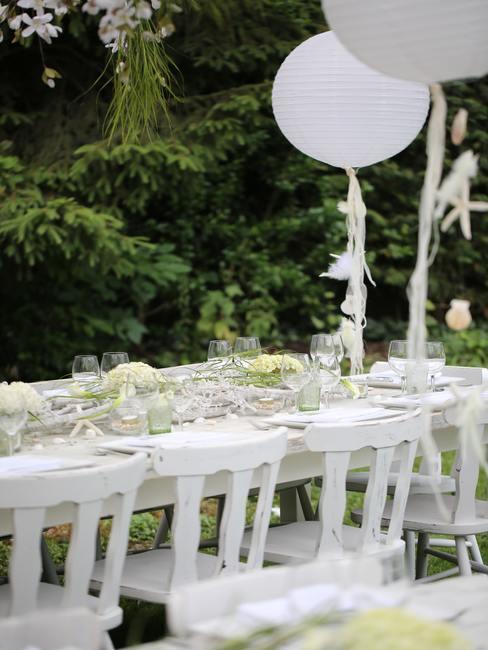 Gedecoreerde tafel voor een communiefeest in de tuin.