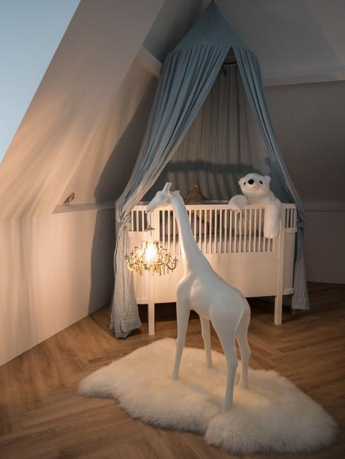 een wit babybed met een grijze hemelvanger