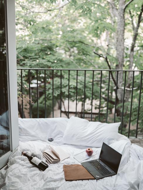 Balkon versierd met wit beddengoed en kussens met een laptop en wijn in een romantisch interieur