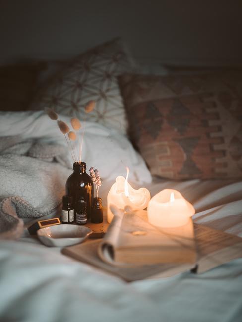 Een bed met wit beddengoed en sierkussens en dienblad met kaarsen in een romantisch interieur