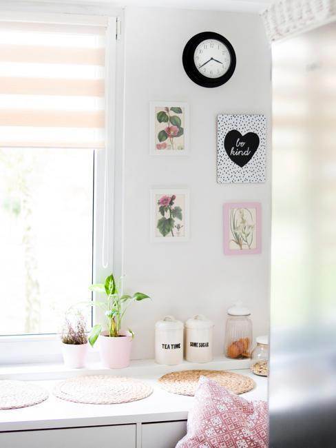 Decoratieve ingelijste prints op witte muur naast een raam