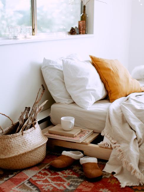 Close-up een bed met wit beddengoed en een decoratief mosterdkleurige kussen en een salontafel met kopje