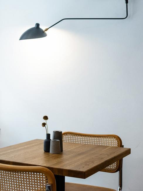 Houten tafel en rotan stoel met minimalistische decoratie in minimalistisch interieur