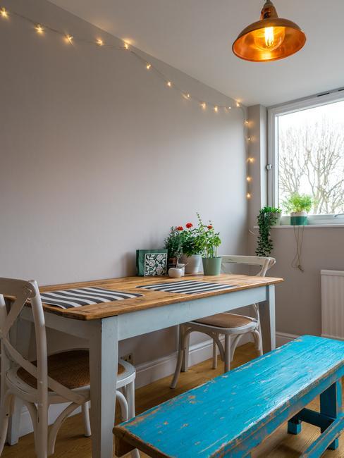 Keuken in wit met een houten tafel en stoelen en een bankje en lichtketting aan het plafond
