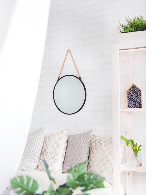 Een decoratieve spiegel aan de muur naast een rek met ornamenten