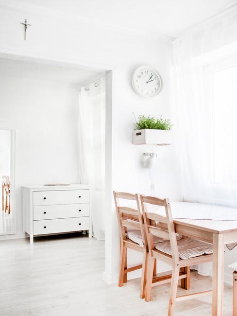 Een kamer met witte muren en gordijnen met een houten tafel en stoelen en een wit dressoir in een modern klassiek interieur