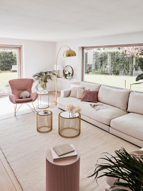 Romantisch-interieur met een beige bank en een roze stoel met een gouden booglamp