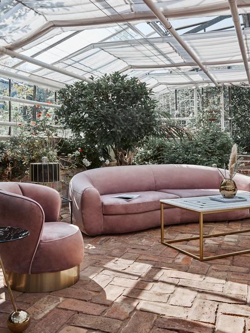 Romantisch interieur in kas met roze velvet bank en stoel