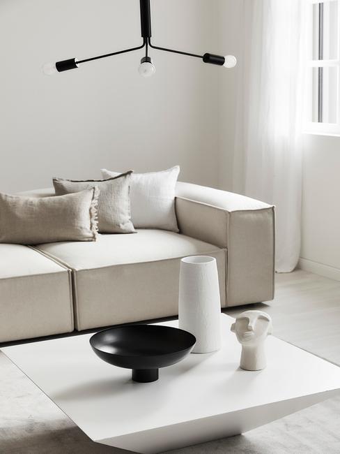 beige lennon bank met een witte salontafel en zwarte hanglamp