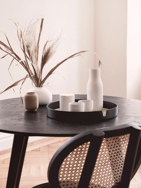 Zwarte ronde tafel met houten stoelen en witte vazen