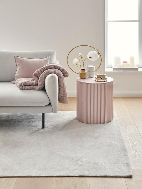 grijze bank met roze kussens en roze ronde bijzettafel