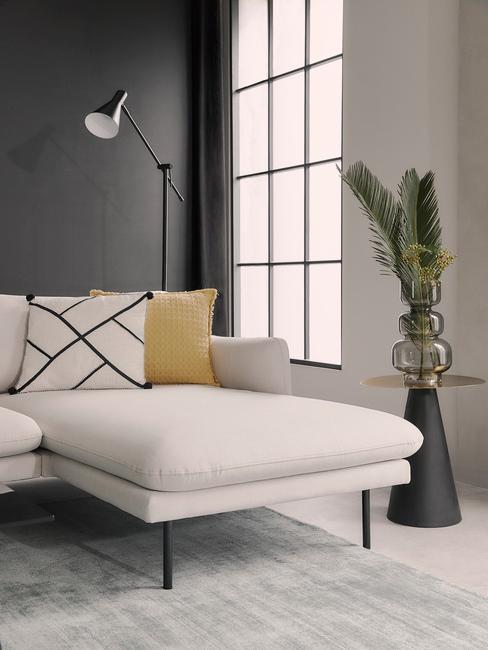 Moderne interieurstijl met beige hoekbank voor grijze muur en zwarte accessoires