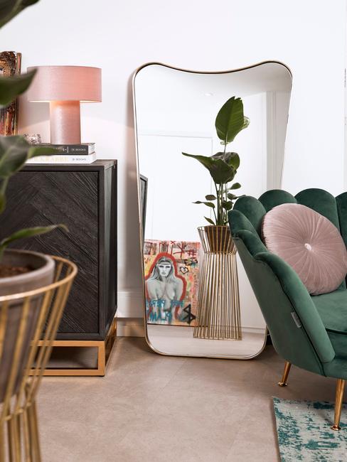 Spiegel staand tegen de muur naas velvet groene stoel