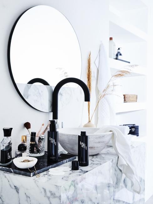 marmere badkamer met een ronde spiegel en een zwarte kraan