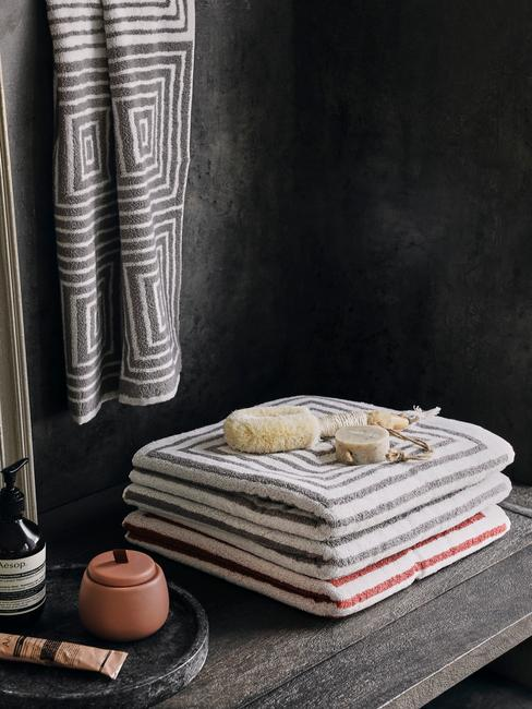 Feng-Shui-Badkamer: met grijze en rode handdoeken in een donkere badkamer van natuurlijke matrialen