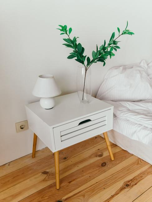 Feng shui huis: een houten nachtkastje met tafellamp en groene tak in transparante vaas