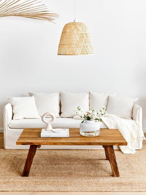 witte bank met een houten tafel en rieten hanglamp