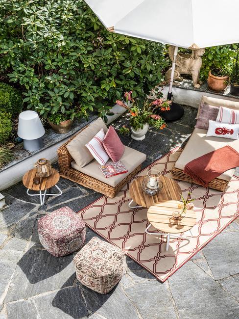 Terras met rotan meubelen, poefs, kussens en outdoor vloerkleed