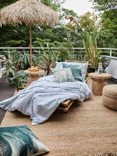 Terras schoonmaken: een ligstoel met plaid en kussens naast groene plantenpotten op het terras