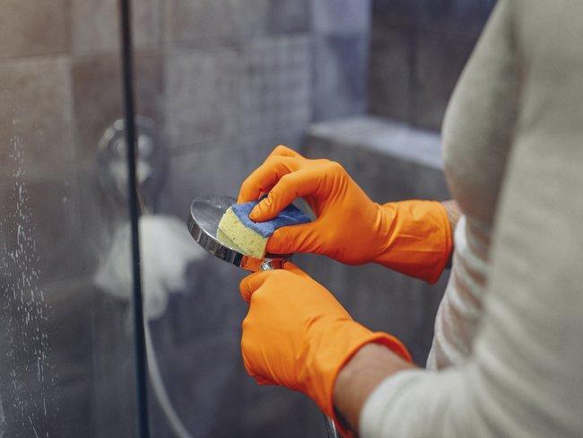Persoon wast douchekop met spons in oranje handschoenen