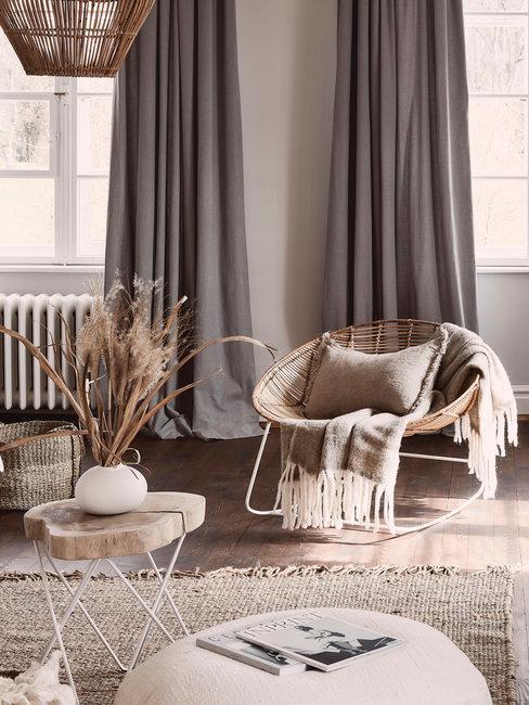 woonkamer met rotan fauteuil, houten bijzettafel met vaas en grijze gordijnen voor raam