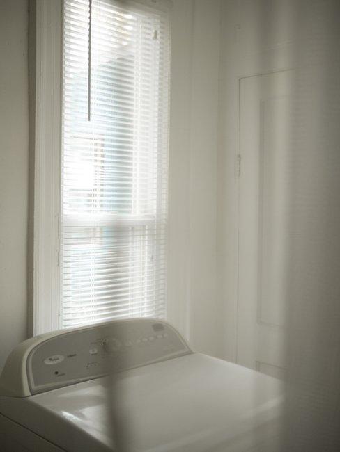 witte wasmachine voor raam met witte jalouzieen