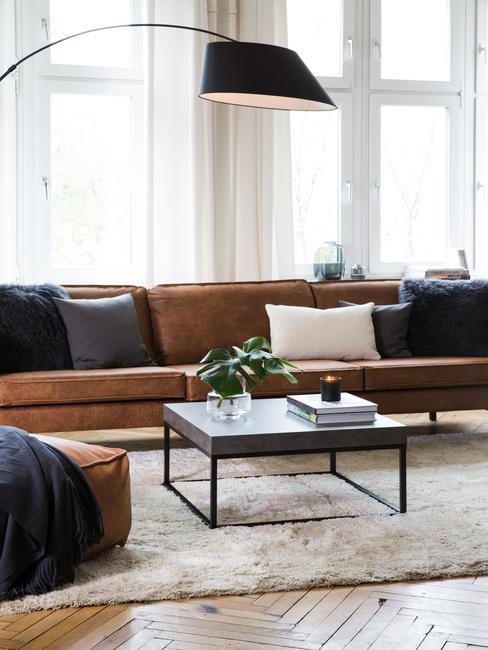Suede schoonmaken: moderne woonkamer met leren zitbank met kussens, zwarte salontafel, leren poef en beige vloerkleed