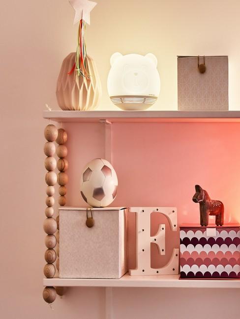 Close-up roze meisjeskamer met accessoires en witte beerlamp