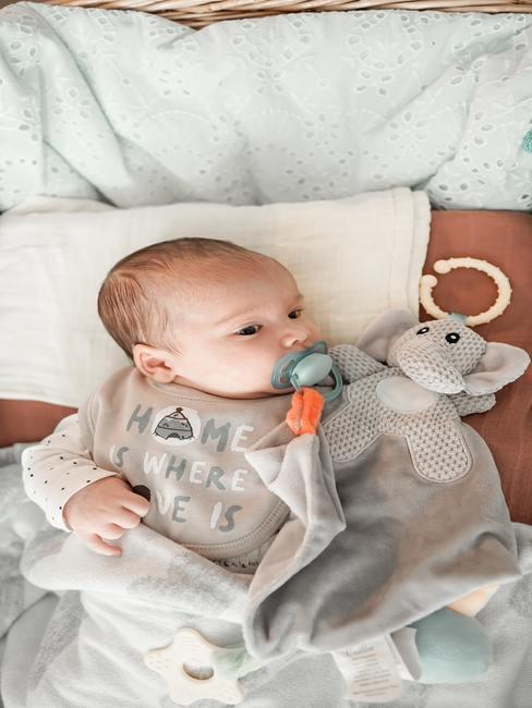 Indeling commode: baby met fopspeen, knuffel en dekentje op de commode