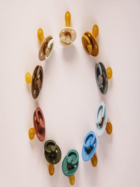 Babykamer okergeel: ring van fopspenen en tuttertjes in verschillende kleuren