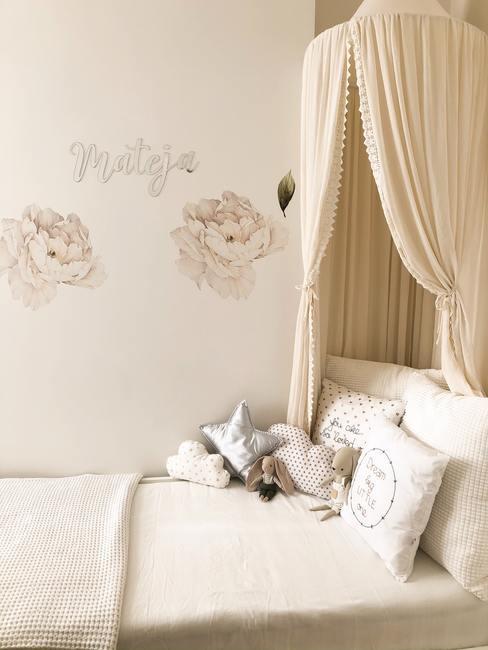 Babykamer in beige tinten met hemelbed en knuffels